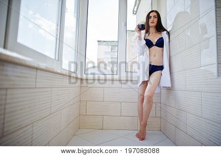 Portrait Of A Lovely Girl In Underwear And Male Shirt Standing With A Glass Of Water In Her Hands On