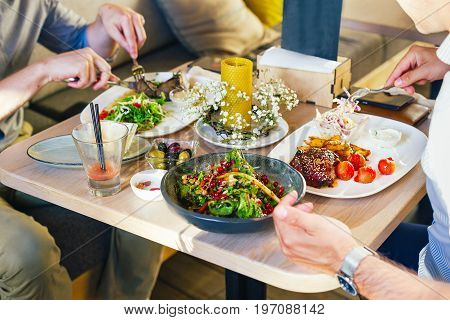 At The Table, Two Men Eat Dinner, Eat A Steak, With A Salad On A White Plate, With A Fork And Knife