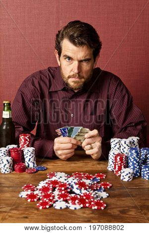man playing poker with credit cards, metaphor for bad debt