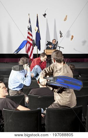 Person on stage having shoes thrown at him to shut him up. All people in shot are the same person.