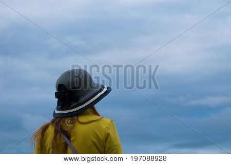 Back view of a girl looking in the distance enjoying view. Sky with a clouds in the background. Girl has nice fashion bow on a hat.