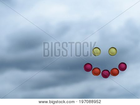 Smile face made of sweet candy contrasting with clouded moody background