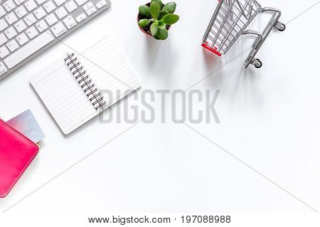Shopping in webstore. Shopping cart, bank card and keyboard on white background top view.
