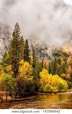 Yosemite National Park Valley and Merced River at autumn. Low clouds lay in the valley. California, USA.