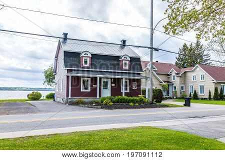 Batiscan Canada - May 29 2017: Red building by the St Lawrence river in small town on Chemin du Roy