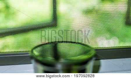 Reflection Of Mesh Window And Green Foliage In Cup Of Water Or Tea On Windowsill