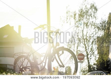 Beautiful modern city urban bicycle parked on a street in calm town with majestic sun flare sunlight behind - sport concept staying fit concept going to work by bike at sunset or sunrise