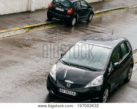 STRASBOURG FRANCE - MAY 30 2016: Rain drops falling over aerial view of a Honda Fit and Citroen C2 parked on French street