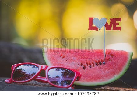 Close up of watermelon slice with love sign on stick and sunglasses on table in the park. Healthy eating and summertime concepts.