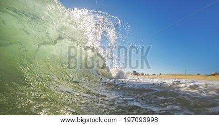 A transparent wave breaks up close-up. Portugal Algarve.
