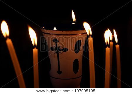 Lampade surrounded by burning candles on a black background