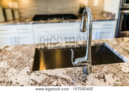 New Modern Faucet And Kitchen Sink Closeup With Island And Granite Countertops
