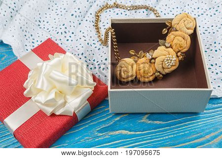 Handmade peach-colored necklace lies in a brown box