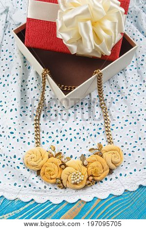 Handmade peach-colored necklace lies on the lacy white fabric near the gift box