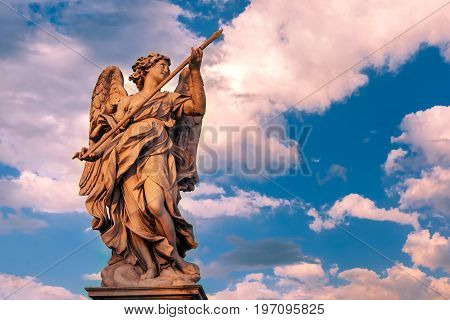 Marble statue of Angel with the Lance at sunset, one of the ten angels on Saint Angel Bridge, symbols of Christ's Passion, Rome, Italy