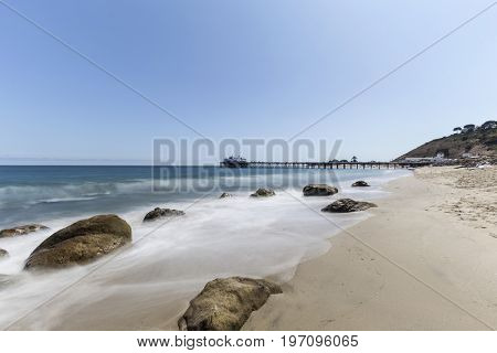 Malibu Pier beach with motion blur surf near Los Angeles in Southern California.