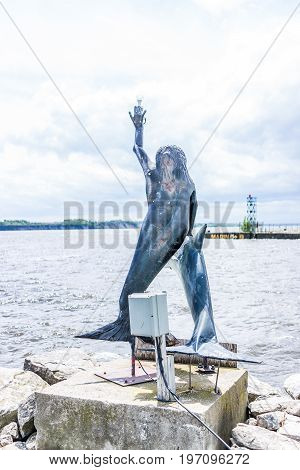 Portneuf, Canada - May 29, 2017: Mermaid And Dolphin Lighthouse Statue On Harbor By Pier In Saint-la
