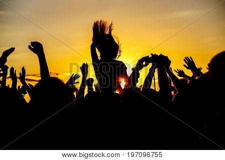 The crowd enjoys the summer music festival, sunset, the silhouettes hands up