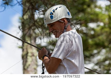 MEZIO, PORTUGAL - JULY 22, 2017: adventurous man prepares to a slide in zip lining thru the forest. July 22, 2017, Mezio, Portugal.