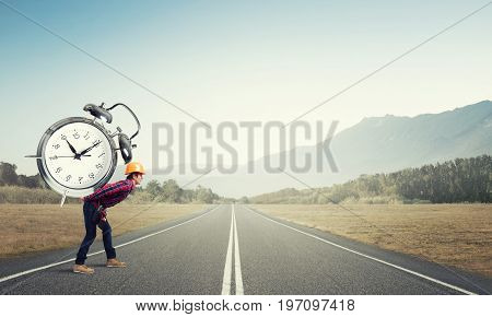 Builder man in helmet carrying alarm clock on back