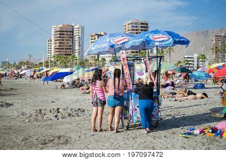 IQUIQUE CHILE 14 JANUARY 2017: women around icecream cart at the city beach