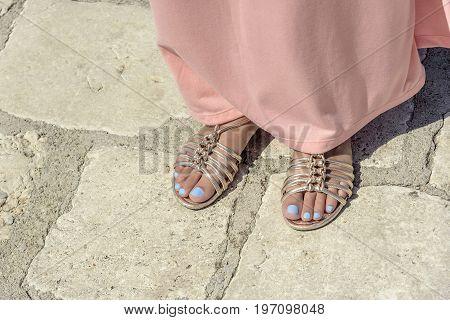 Female legs in sandals on legs close-up.