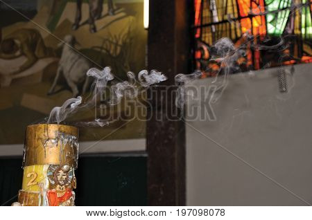 Niteroi, Brazil - January 26, 2013. Close-up of smoking candle with image of Jesus Christ in the Santuário das Almas church, in the coastal city of Niteroi. Located in the Rio de Janeiro State, southwestern Brazil