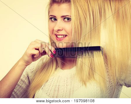 Blonde Woman Brushing Her Long Hair With Comb