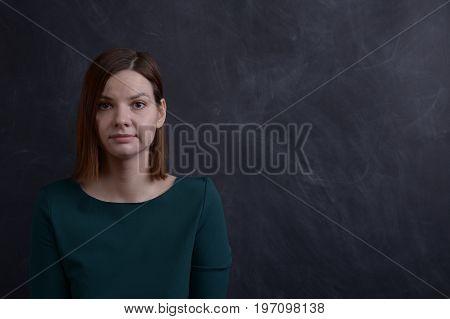 Girl in green dress at school board.