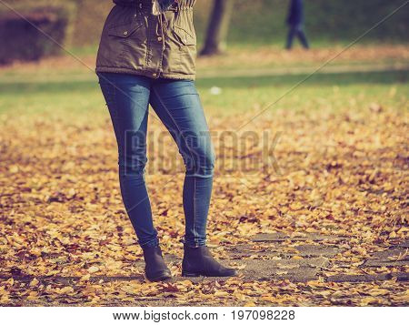 Woman legs standing in autumnal park during autumn weather gold seasonal leaves on ground.
