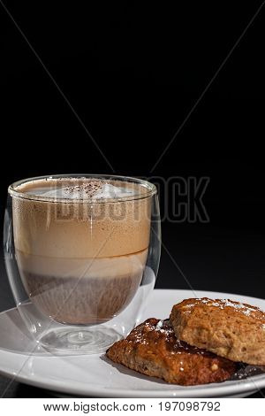Coffee and biscuits. Cappucino in double walled glass mug with home made cookies. Close up against black background with copy space.