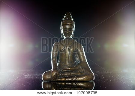 Traditional buddha figurine in meditation pose. Bronze buddhist statue backlit to show spiritual enlightenment.