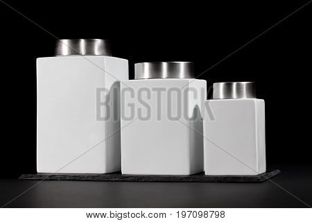 Modern ceramic storage jars. Set of three kitchen food containers in descending height. Simple and aesthetic chrome and white jars with a modernistic design.