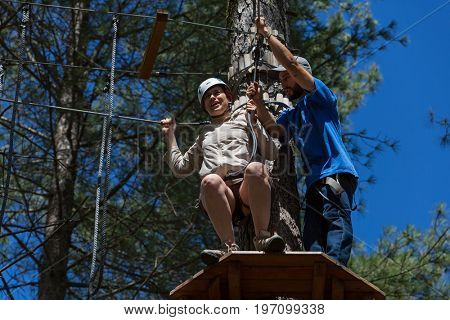 MEZIO, PORTUGAL - JULY 22, 2017: adventurous woman prepares to a slide in zip lining thru the forest. July 22, 2017, Mezio, Portugal.