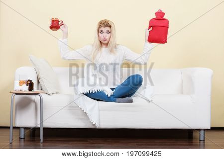 Woman Holding Hot Water Bottle And Tea In Cup