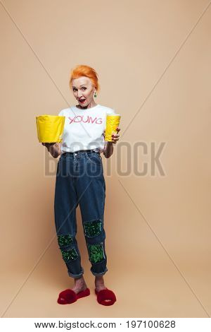 Image of amazing mature redhead fashion woman standing isolated at studio eating popcorn and drinking aerated water. Looking camera.