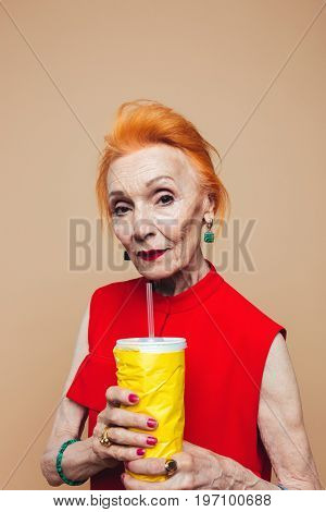 Image of serious mature redhead fashion woman standing isolated at studio drinking aerated water. Looking camera.
