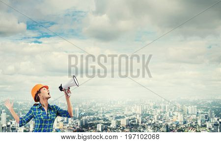 Engineer woman with megaphone on modern city landscape