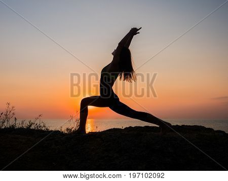 Morning exercise. Twine. Yoga mat woman stretching hip, hamstring muscles and groin area. Fit fitness athlete girl exercising sports stretches in active wear on beach at sunset. poster