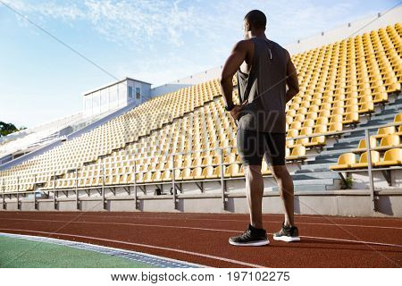 Back view full length of a young african male athlete standing on a race track at the stadium