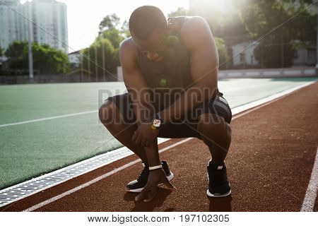 Young tired african male athlete finished running and resting while sitting on a racetrack
