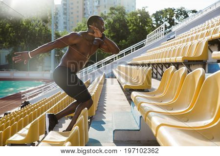 Side view of a muscular healthy african man athlete running upstairs at the stadium