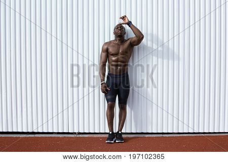 Full length of an exhausted afro american male athlete with water bottle standing against white wall