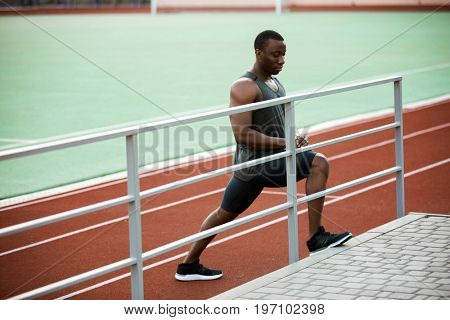 Young concentrated african male athlete stretching legs before the competition at the stadium