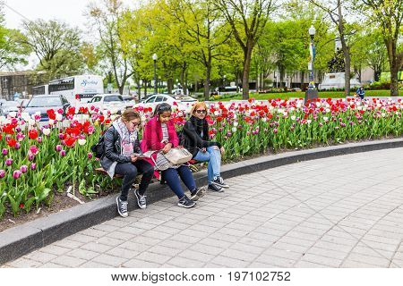 Quebec City, Canada - May 29, 2017: Tulip Flowers And People Sitting On Bench In Summer By Roundabou