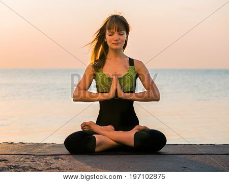 Young caucasian woman in black swimsuit relaxing by practicing yoga on the nature near sea at summer, close-up of hands, namaste and lotus position.