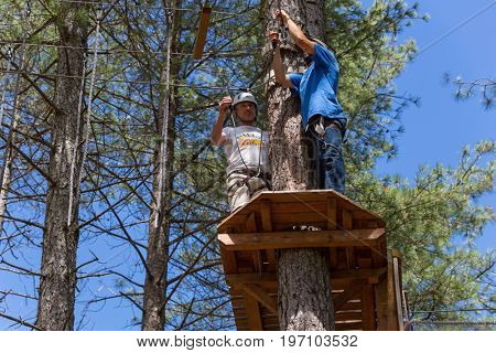 MEZIO, PORTUGAL - JULY 22, 2017: young adventurous man prepares to  slide in zip line thru the forest. July 22, 2017, Mezio, Portugal.