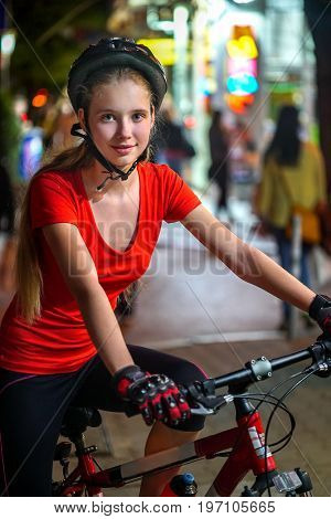 City night bicycle ride. Girls wearing bicycle helmet. Nightlife and passer people in city background. Bright storefronts in the background.