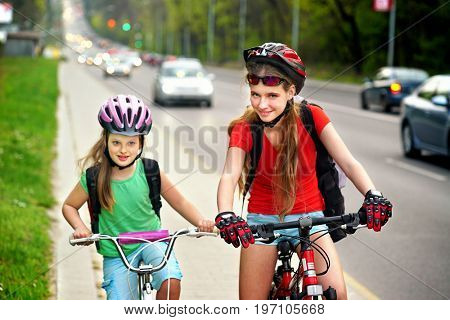 Bikes bicyclist girl. Girls wearing bicycle helmet and glass with rucksack ciclyng bicycle. Girls children cycling on bike lane Friendship between children of different ages There are cars on the road