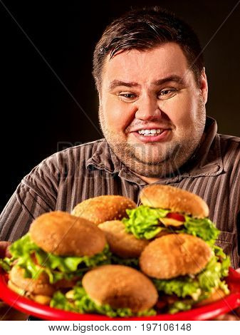 Fat man eating fast food hamberger and carries treat for friends on tray. Breakfast for overweight person. Poor food leads to obesity. Person regularly overeats concept on black background.